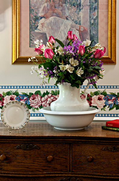 White vase in bowl on table with freshly cut flowers, flowered wallpaper border.