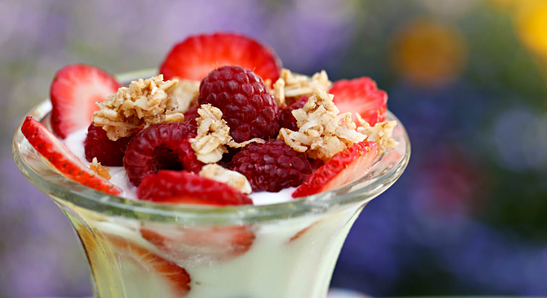 Parfait dish with fresh raspberries, strawberries and sprinkled with coconut.