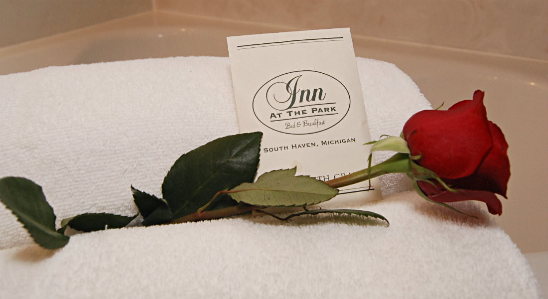 Red rose laying on white town on edge of tub, Pouch with Inn At The Park bath crystals.