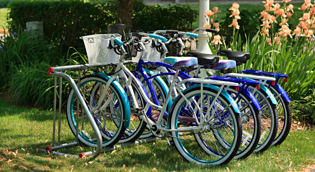 Group of blue locked bikes with woven baskets hooked to bike rack.