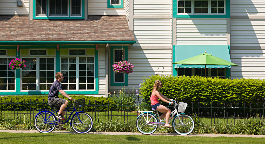 Man and woman riding bikes along property, bed and breakfast in the back surrounded by trees and hanging flowers.