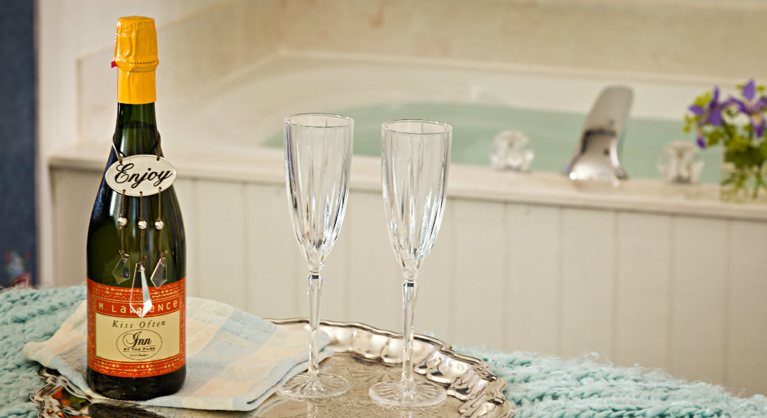 Cream oval filled tub, silver serving tray with champagne bottle and crystal flutes.