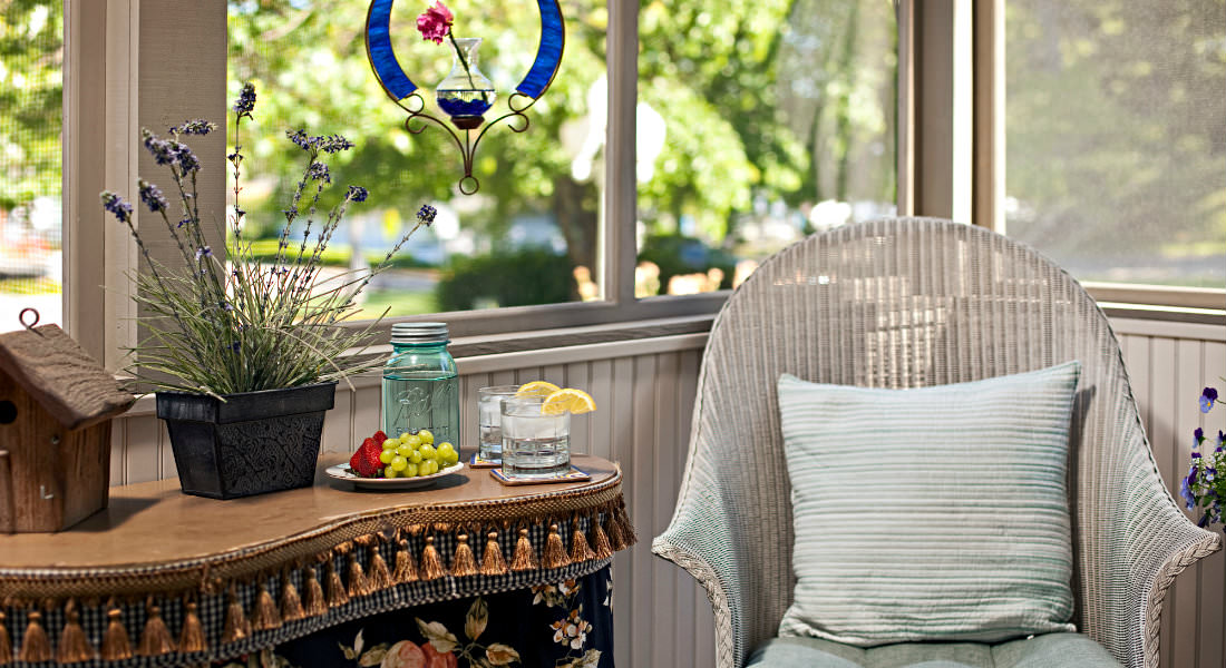 White wicker chair in sunroom with large windows, water glasses and mason jar pitcher, plate with grapes and strawberries.