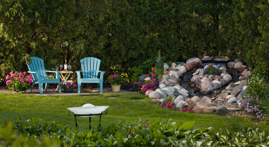 Two blue adirondack chairs in garden by woods, rock fountain surrounded by flowers
