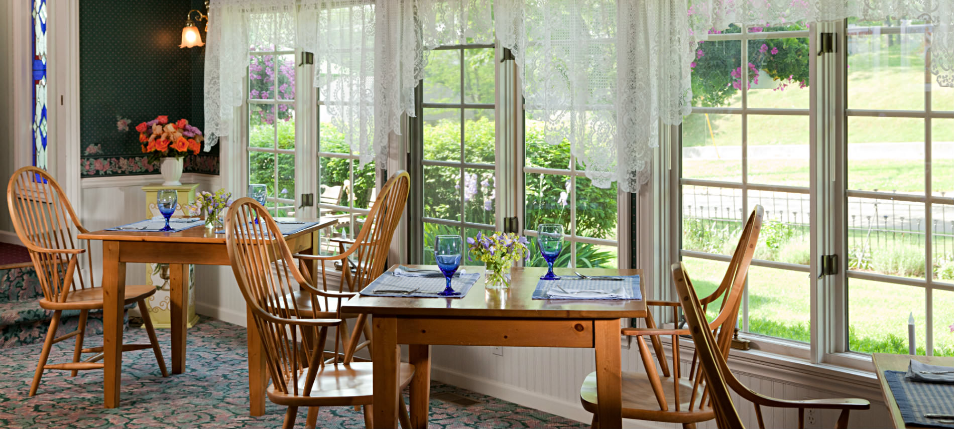 Wooden dining tables and chairs set for breakfast with blue glasses, White lace curtains. green shurbs, blue flowered rug.