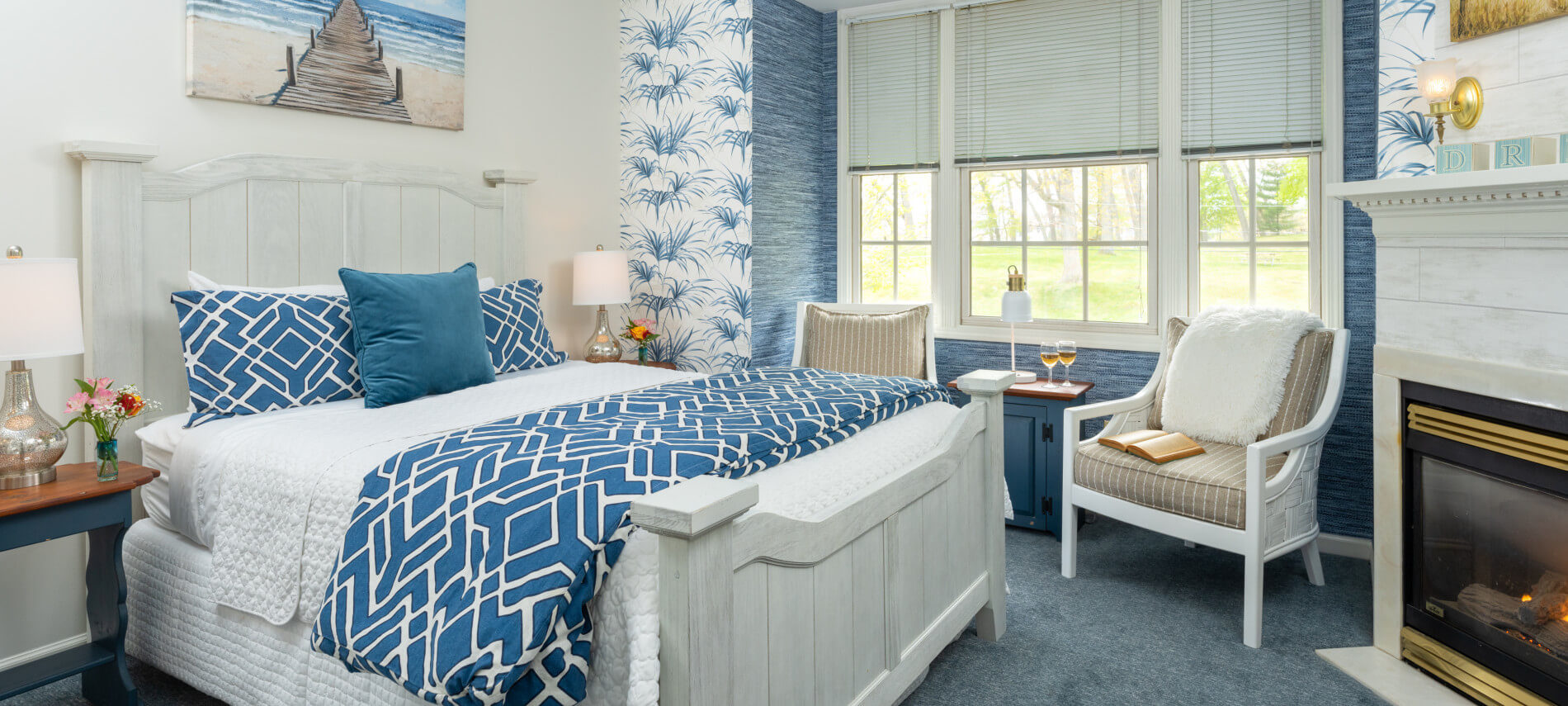 Queen bed with white wood frame and blue comforter, cushioned white wicker chairs by windows, blue carpet, fireplace with cream mantel.