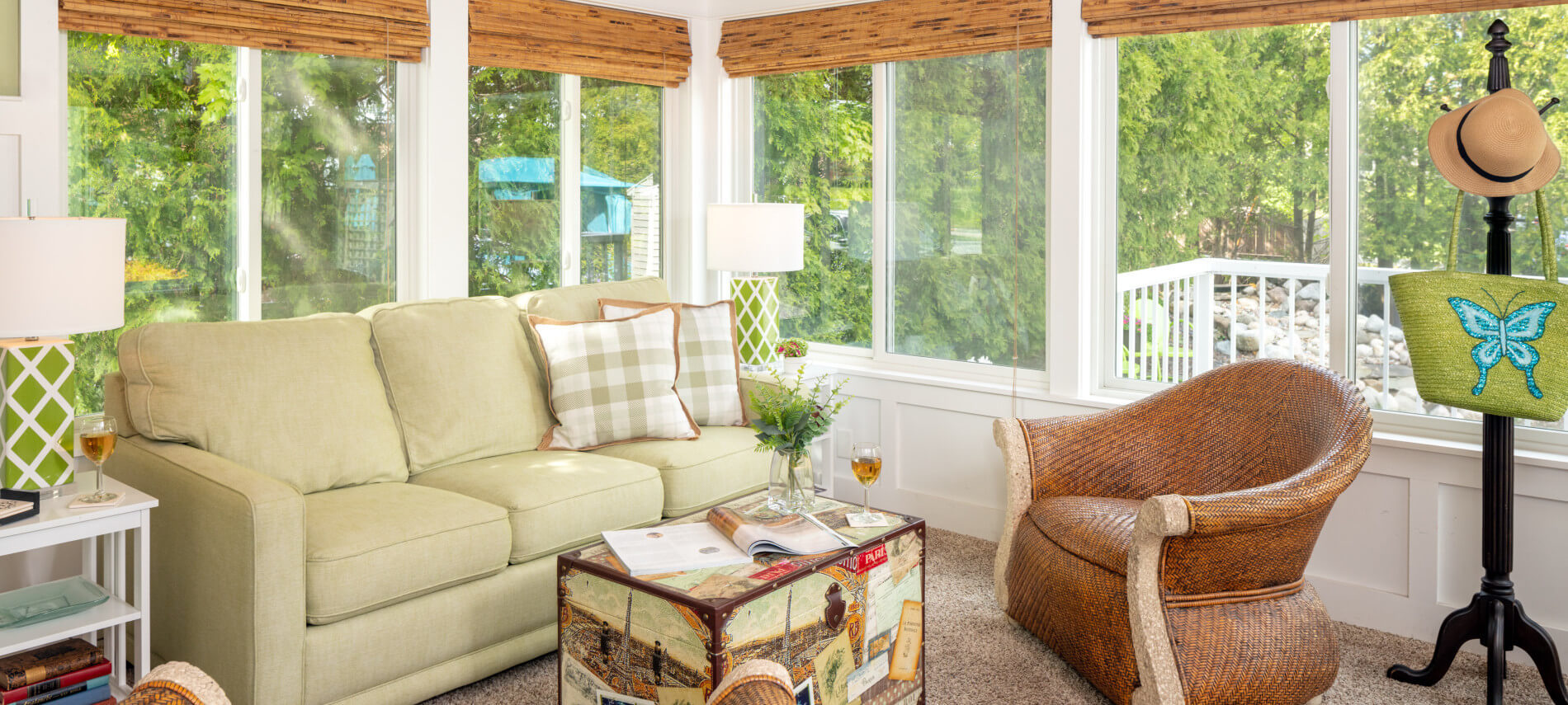 sunroom with cream couch and brown chairs with table in middle holding wine glasses, window with brown shades, coat rack with straw hat & bag with butterfly
