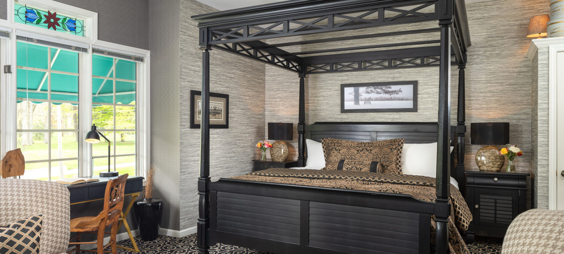 King sized four poster iron bed, tan wallpaper, stands with lamps, checkered chairs, stand with champagne glasses, desk facing window, black carpet.