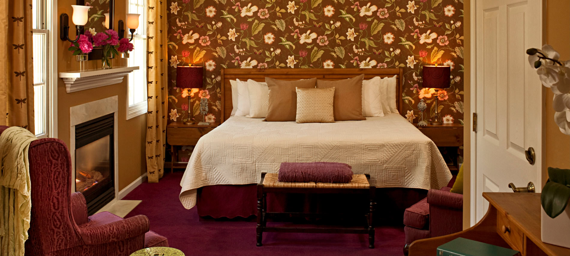 King bed with cream bedspread and pillows, brown walls and flowered wallpaper, fireplace, burgundy chair and carpet, stands with lamps.