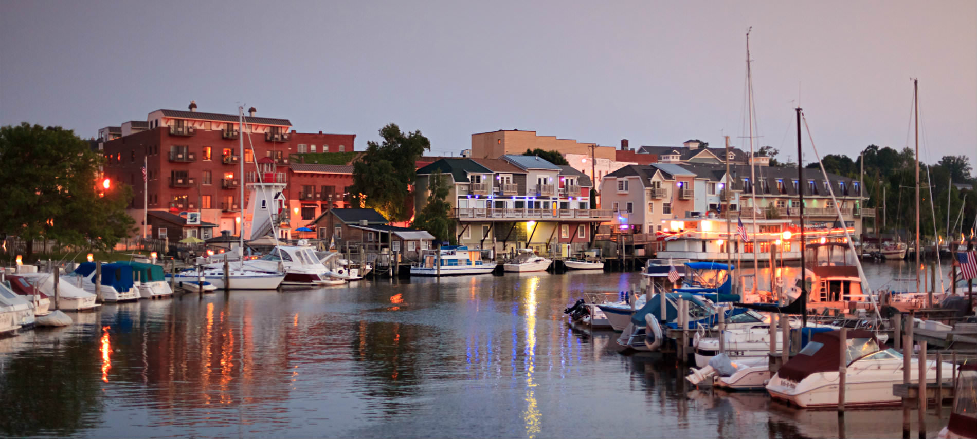 Well-lit buildings along waterfront at dusk, boats docked with lights shining off water, trees in distance.