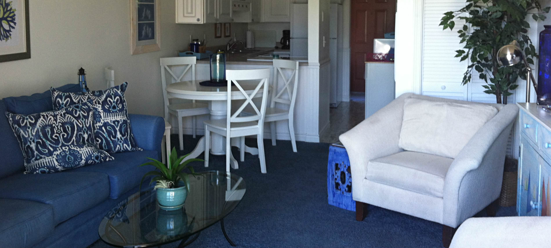 Round white table with 3 chairs, blue couch with pillows, white chair, kitchette.