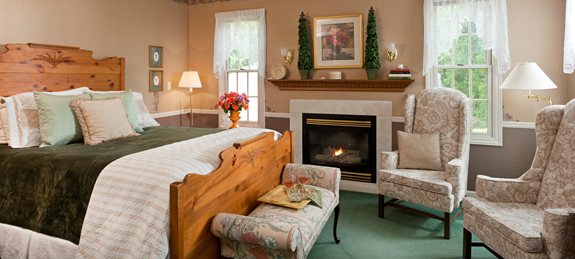 King sized bed wooden head and footboards, green comforter, two cream chairs by fireplace between windows with lace sheers.