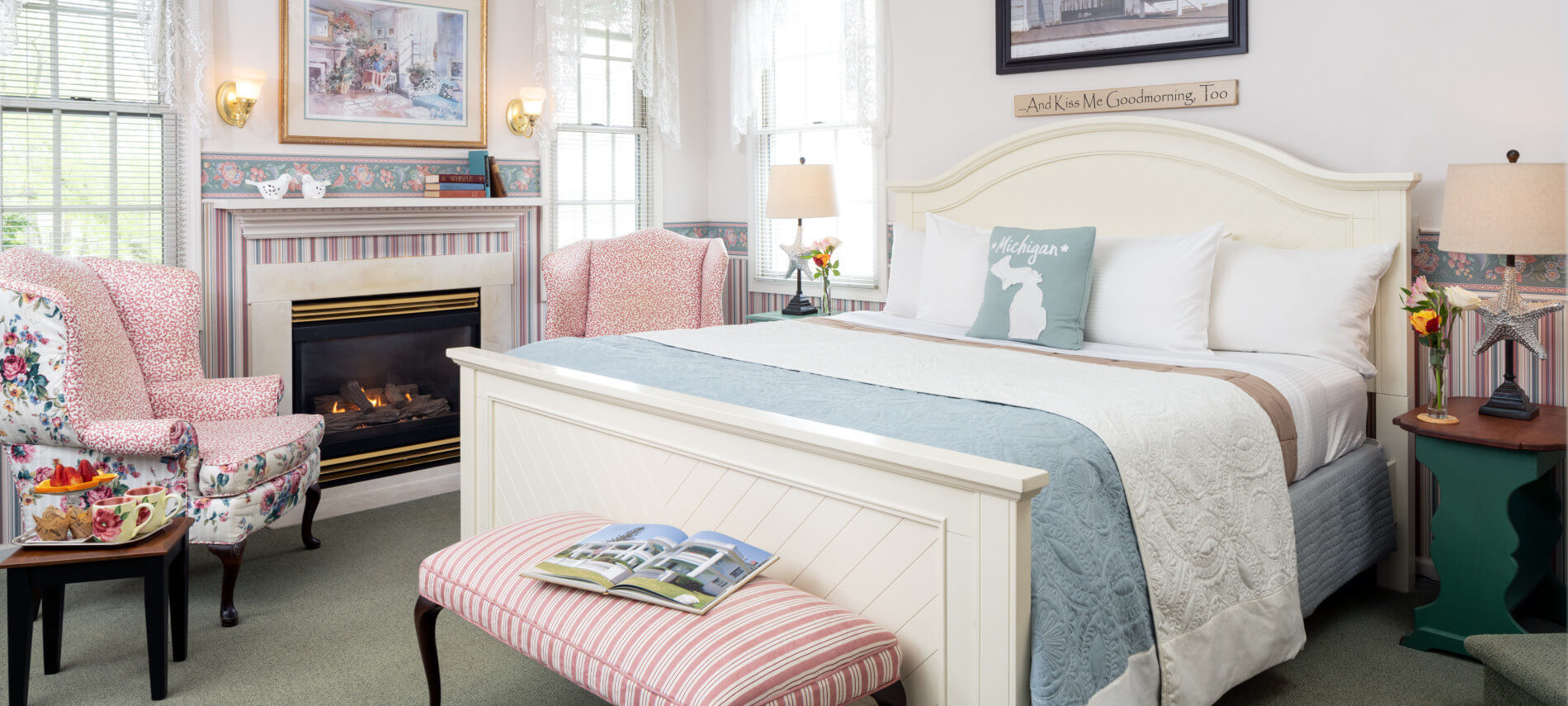 white king size bed with blue coverings, fireplace, flowered Queen Anne Chairs, three windows with lace sheers, striped bench