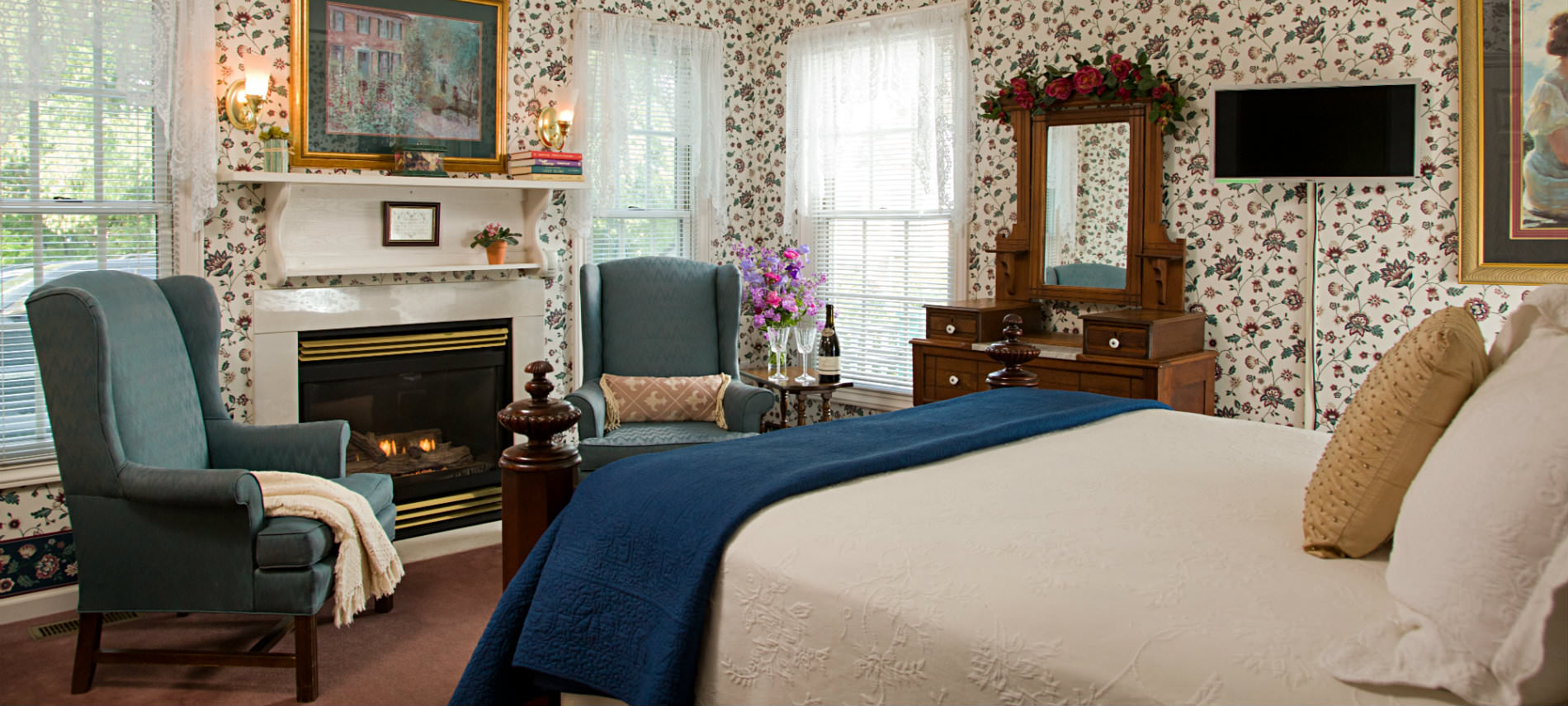 Queen sized bed in flowered wallpaper brightly lit room, fireplace, two green Queen Anne Chairs, brown carpet.