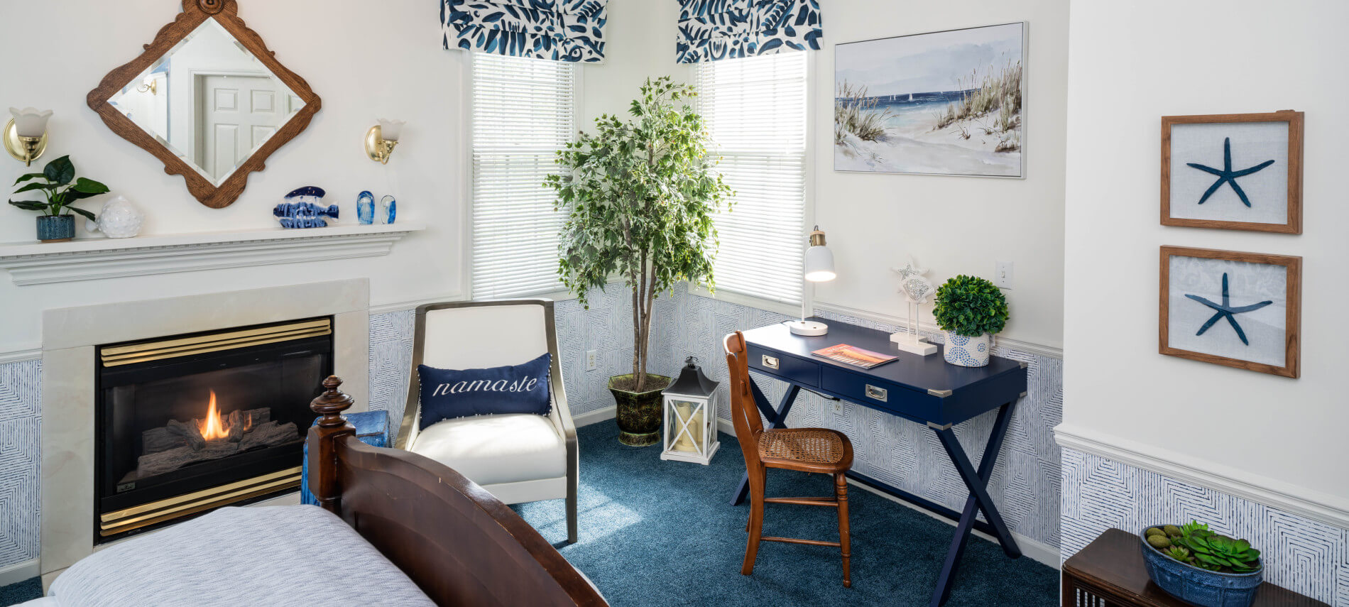 Queen cherry bed with white bedspread, two maroon chairs by fireplace, lace curtains on window, oad dresser with flowers.