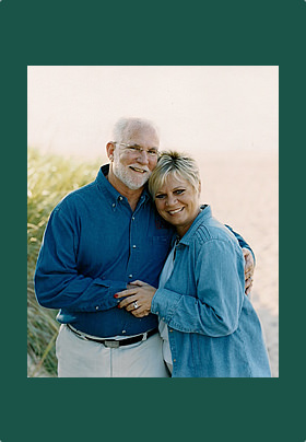 Green-Matted Picture with greenery in back, man and women with blue shirt hugging