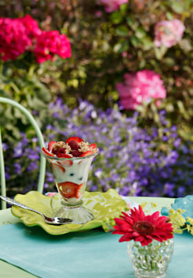 Parfait in sundae dish on yellow plate with strawberries surrounded by multi-colored flowers and greenery.