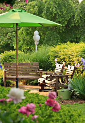 Wooden bench and chairs in garden, green umbrella surrounded by flowers, bushes and trees.