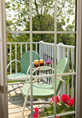Private patio with white railing and green chairs surrounded by woods, stand with candles, red potted flowers.