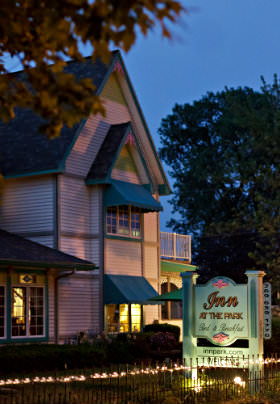 "Exterior view of the Inn at dusk with lights on inside, and a light shining on the ""Inn at the Park Bed & Breakfast"" sign out front."