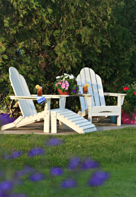 Two white Adirondack chairs and table on small patio surrounded by lush green grass and trees and some colorful potted flowers.