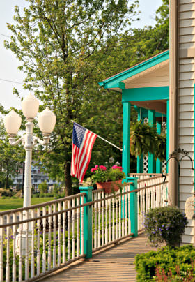 Exterior view of the Inn: white lamp post, tan siding, spindle railing, and covered porch with aqua trim and hanging plants