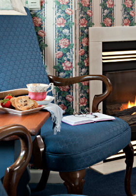 Blue chair by stand with tray containing teacup and homemade chocolate chip cookies & strawberries, fireplace, fowered wallpaper.