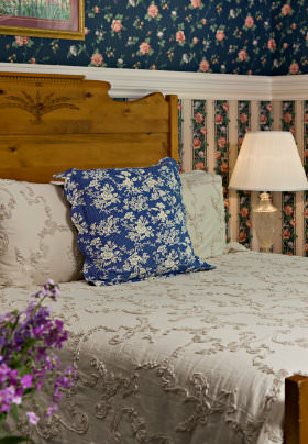 Corner view of Queen bed with tan bedspread, stand with lamp, flowered wallpaper, purple flowers on stand.