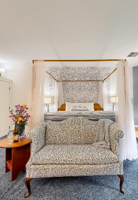 Two White Queen Anne Chairs with flowers by windows, Blue wall with pictures, Blue Carpet and loveseat, Ceiling Fan.