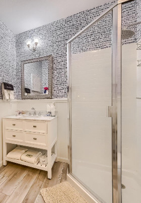 Old-Fashioned White Washstand with sink. Lights over Mirror on blue striped wallpaper, towel rack with blue hand towels.