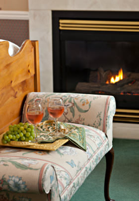 Flower cushioned bench, wicker tray with grapes and red wine glasses by fireplace.
