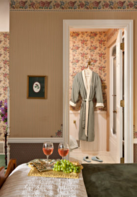 Wicker tray with green grapes and red wine glasses, tan walls with flowered wallpaper border, view into bathroom, green robe.