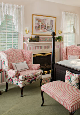 Pink flowered Queen Anne chairs by windows, fireplace, pink striped material covered cherry bench, painting over fireplace