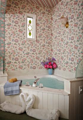 Corner Jacuzzi filled tub, swan sculptures, pink flowered wallpaper, stain-glass window, flowers in corner.