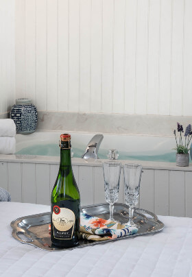 Marron chairs by fireplace between plaid curtained windows, blue bend with opened book at foot of bed.