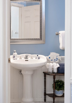 White pedestal sink with mirror, pink and blue plaid wallpaper, stand with blue and white towels.